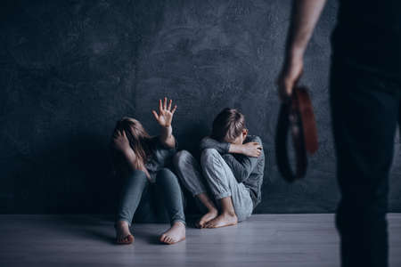 Domestic violence, children hiding from strict punishment in dark room Stockfoto