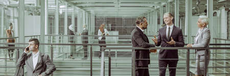 Business partners negotiating in modern interior, panorama