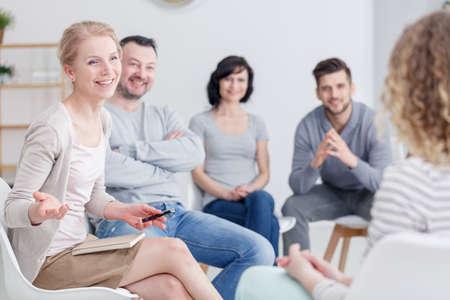 Terapista femminile sorridente che parla con la gente nel gruppo di sostegno, sedentesi con un taccuino Archivio Fotografico - 85751154