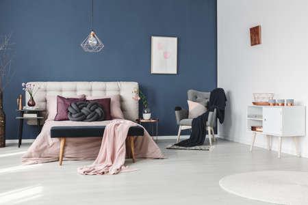 Kaarsen op witte commode in pastel slaapkamer met decoratieve koperen plaat op witte muur