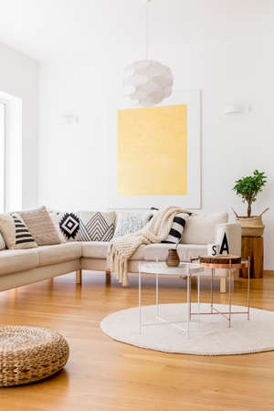 living room window: Plant in braided basket on wooden stool in living room with gold painting on white wall