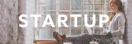Schreiben 'Startup' und junge schöne Frau sitzt auf Fensterbrett mit ihrem Laptop
