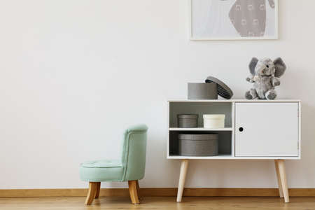 Green chair next to white shelf with boxes and plush toy in scandinavian style kids room