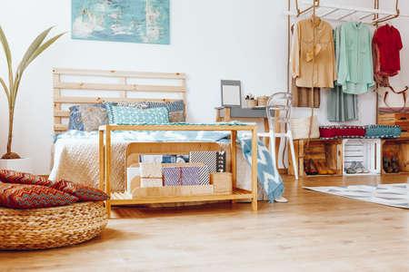 Patterned pillows on braided pouf near to wooden cupboard with newspaper Lizenzfreie Bilder
