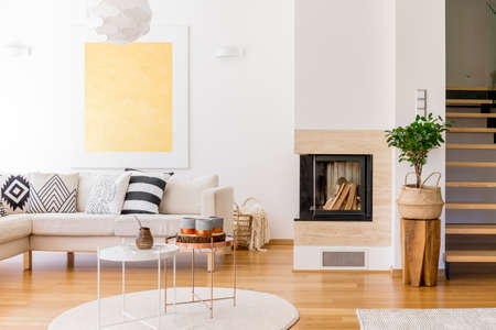living room window: Copper coffee table on white carpet in living room with fireplace and gold painting on wall Stock Photo
