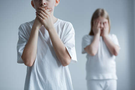 Child bullying problem, isolated tormented children covering faces, white background Imagens