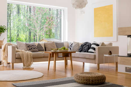 Beige couch set in scandinavian style living room in spacious house with view on forest
