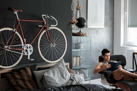 bedroom design: Red bike on wooden bolster of king-size bed in mannish room with black globe on metal shelf Stock Photo
