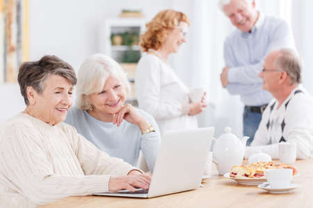 Two positive senior women using laptop, surfing the internet at nursing home with company of elderly friends talking in the blurred background Zdjęcie Seryjne