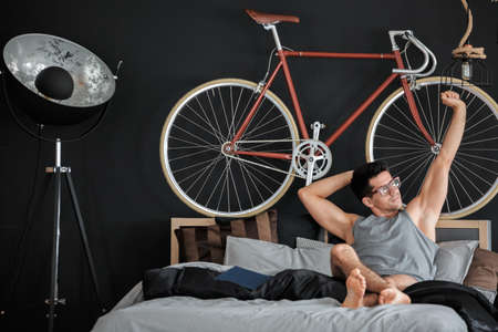 Man in glasses lies on king-size bed during free time in bedroom with red bike and design lamp