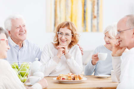 Happy elderly couple talking and laughing at tea party with friendly senior neighbors Zdjęcie Seryjne