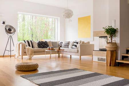 Gestreifter grauer Teppich und geflochtener Puff auf Plattenboden im skandinavischen Artwohnzimmer Standard-Bild - 85534882
