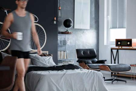 Metal shelf with black globe against concrete wall with white picture in manly bedroom
