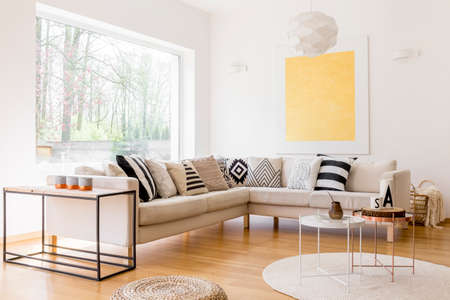 Three candles on shelf next to beige couch set with patterned pillows in living room