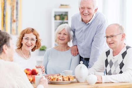 Gruppo di anziani sorridenti seduto al tavolo con tè e torta, raccontando barzellette e relax a casa di riposo per gli anziani Archivio Fotografico