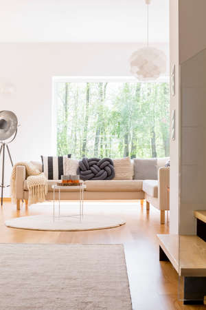 Comfortable sofa and designed lamp in spacious living room with view on forest Lizenzfreie Bilder