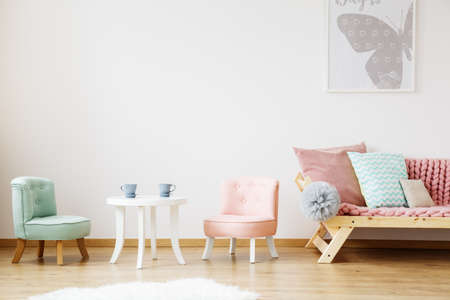 Blue cups on white childrens table and chairs in scandinavian style kids room Lizenzfreie Bilder