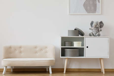 Designed white sofa near white shelf with plush toy and boxes in monochromatic kid room