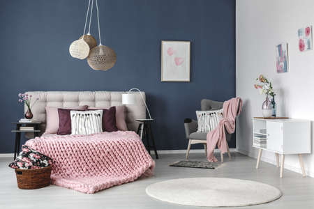 Grey armchair with pink blanket and white pillow in the corner of pastel bedroom with designed lamp