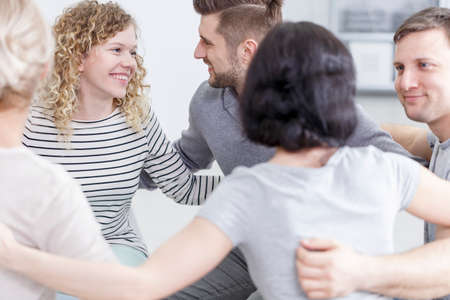 Group of smiling young people in embrace after successful therapy Stock Photo