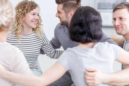 Gruppe von lächelnden jungen Menschen in Umarmung nach erfolgreicher Therapie