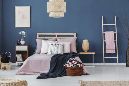 Pink towel on ladder next to bedside cabinet with design lamp in bedroom with king-size bed Lizenzfreie Bilder