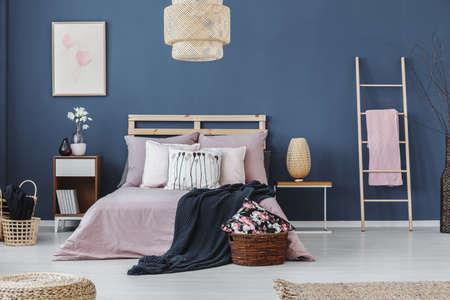 Roze handdoek op ladder naast nachtkastje met designlamp in slaapkamer met king-size bed