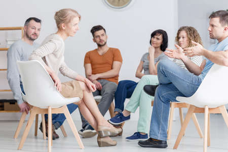 Man and woman having coaching session about assertiveness in group of people Standard-Bild