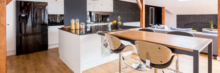 Open luxurious loft house interior with modern dining area, wooden metal table and chairs, kitchen with island and living room with couch Lizenzfreie Bilder