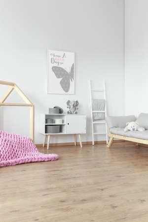 Pink braided blanket on floor and grey picture above white shelf with plush toy Lizenzfreie Bilder
