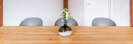 Panorama photo, a glass vase of flowers placed on wooden table with modern gray chairs, interior design of cozy dining room with light pastel wall and door