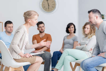 Middle-aged couple talking and solving problems during group assertiveness training