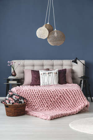 bedroom design: Pink braided blanket on king-size bed in bedroom with designed lamp and blue wall Stock Photo