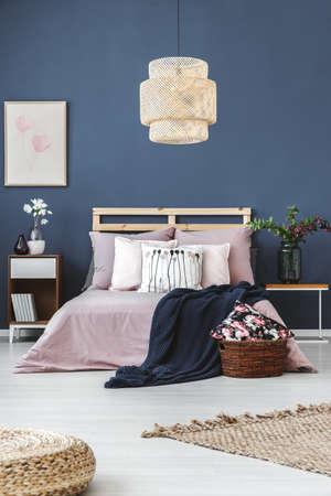 Poef en tapijt op witte vloer in pastel slaapkamer met witte bloemen in vaas op houten plank