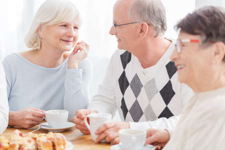 Close up of happy senior couple in love smiling, looking at each other, holding cups of coffee during meeting with elderly friends