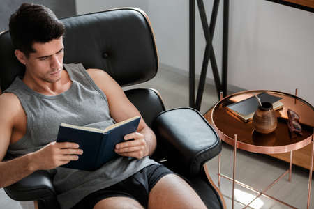 Man sits on leather chaise lounge while drinking yerba mate and reading book in home office Lizenzfreie Bilder