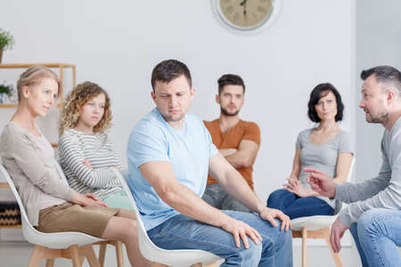Unhappy man during AA group therapy with caucasian people