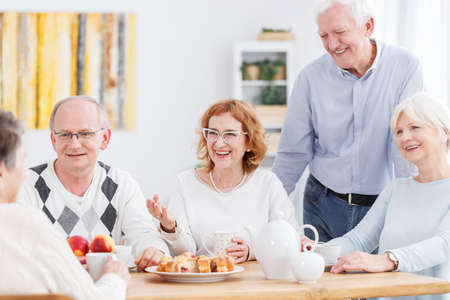 Old people activity concept, group of happy senior friends chatting and drinking tea, sitting at table during their meeting at home Zdjęcie Seryjne