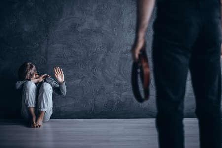 Padre siendo físicamente abusivo hacia su hijo, sosteniendo el cinturón