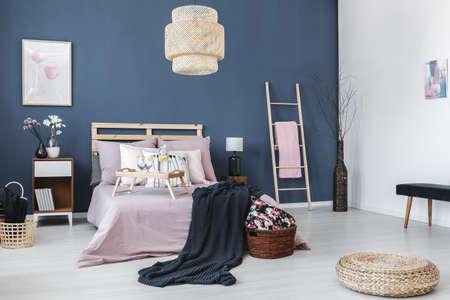 Nachtkastje met zwarte lamp tussen ladder met roze handdoek en kingsize bed tegen blauwe muur