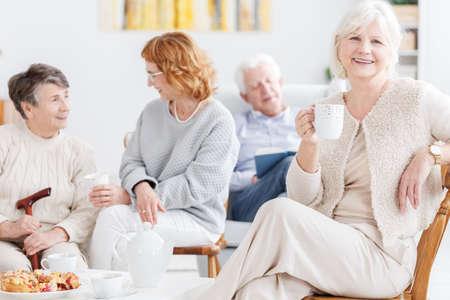 Bejaarde vrienden die middag doorbrengend samen spreken en ontspannend, nadruk op glimlachende grootmoeder die een kop thee hebben