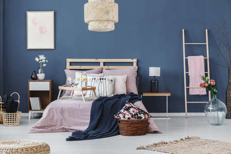 Breakfast tray on king-size bed with pink coverlet and dark blue blanket between bedside cabinets