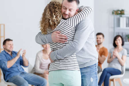 Man and woman hugging during therapy with applauding group of people Lizenzfreie Bilder