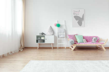 Bright kid room with colorful pillows on couch and simple grey poster on white wall Zdjęcie Seryjne