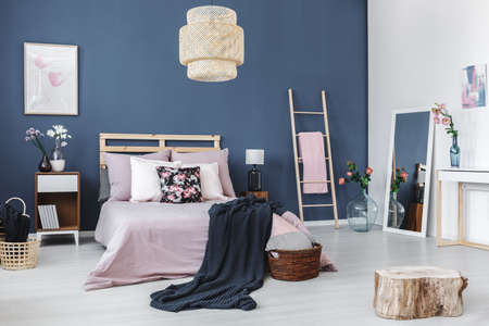 青い壁にシンプルな白い絵とパステル調のベッドルームで光沢のある床の上に木製のスツール