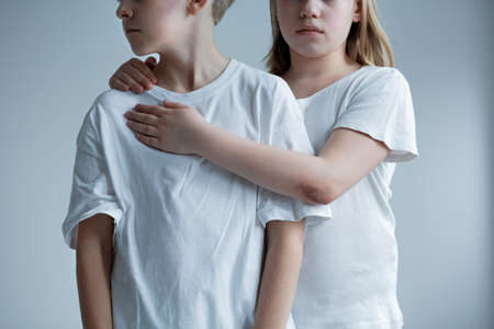 Distrustful little boy and girl, witnessing domestic violence at home