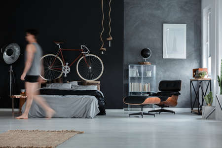 Spacious multifunctional bedroom with black leather chaise lounge and red bike on bolster Lizenzfreie Bilder
