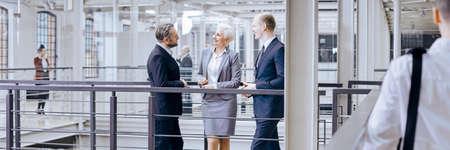 Female boss and her workers talking in stylish office interior Lizenzfreie Bilder