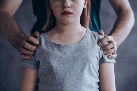 小さな泣いている女の子の男性の手、子供の搾取の概念