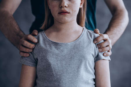 Male hands on little crying girl, concept of children exploitation